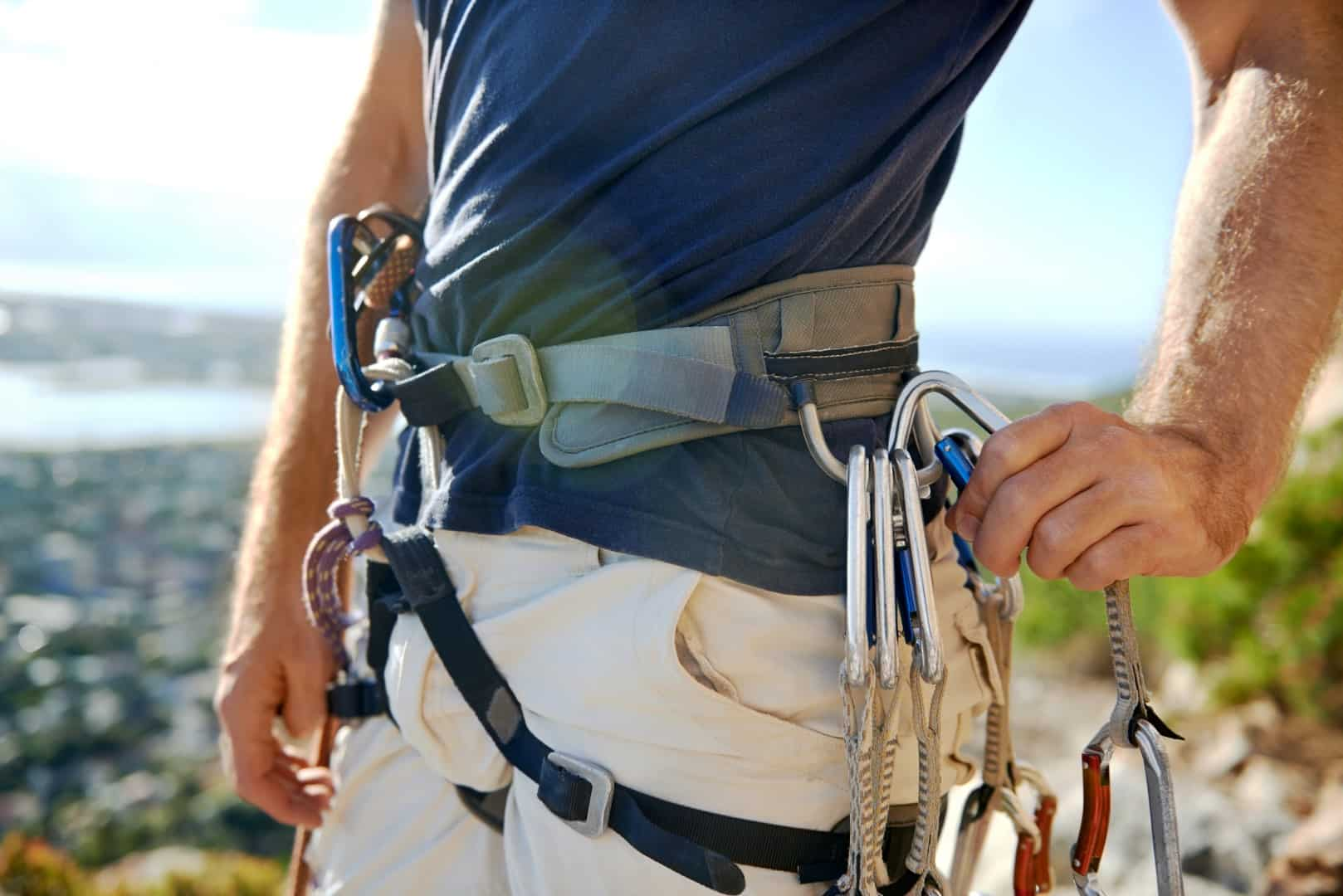 Man with climbing harness and rock climbing equipment