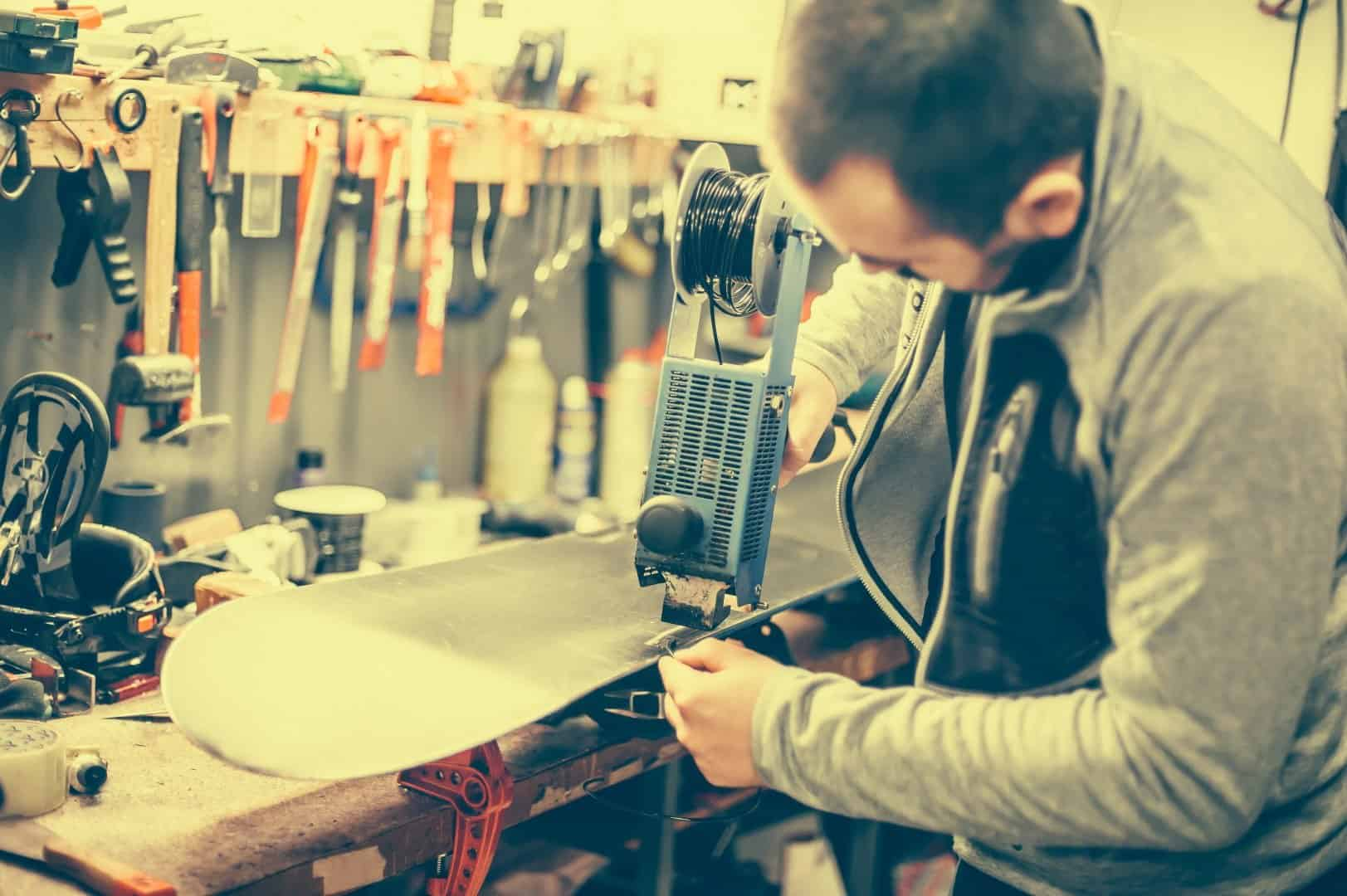Waxing a snowboard on a repair shop